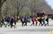 A line of students cross Osborn Drive as CyRide buses make stops