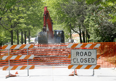"excavator digs up road surface behind ""road closed"" sign"