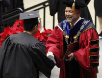 President Steven Leath congratulates a male graduate