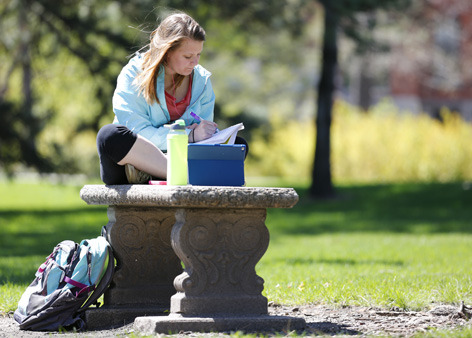 female student studying outdoors on a bench