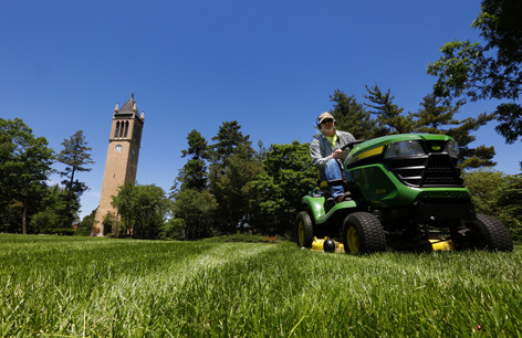 groundskeeper on riding lawnmower with ISU campanile in the back
