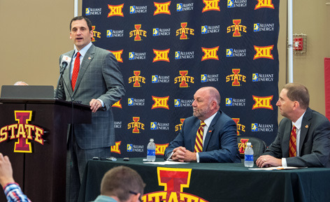 Steve Prohm speaks at a podium with Steven Leath and Jamie Polla