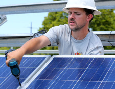 Worker attaches solar panel to rack