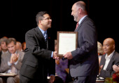 Faculty member Ajay Nair receives his award from President Steve
