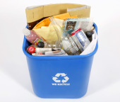 blue recycling bin filled with various papers and beverage conta
