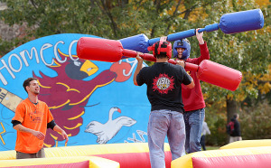 Students compete on inflatable games set up during homecoming.