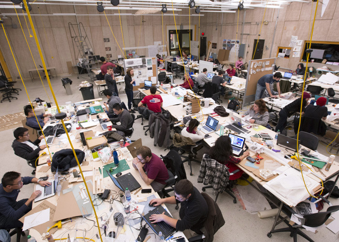 Large studio filled with students working at tables.