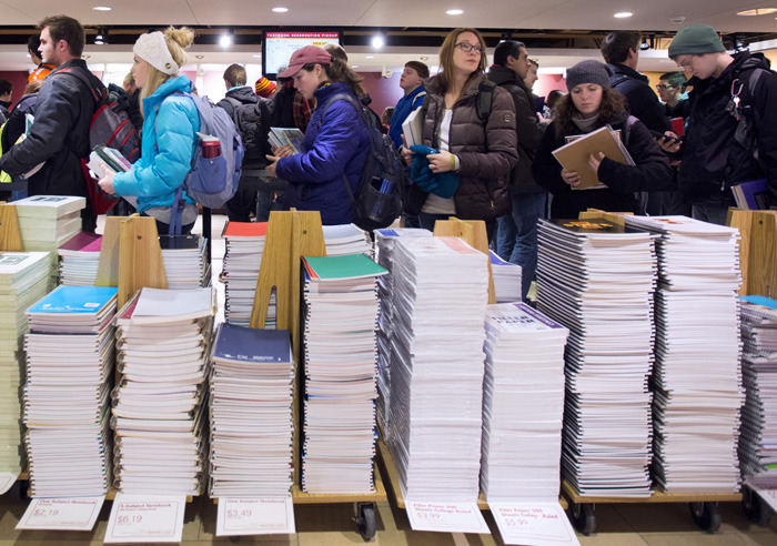 Students in line behind stacks of notebooks