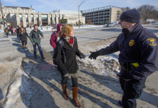 Ames police officer hands card to female student