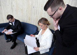 Two male and one female students consult their job fair notes.