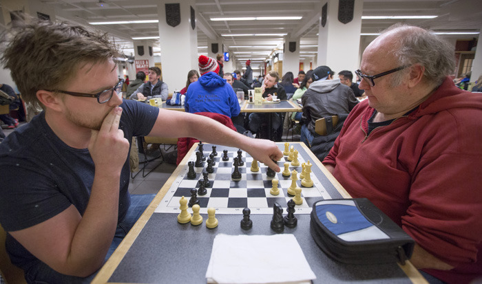 Two men play chess in the Memorial Union food court area