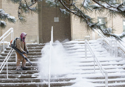 Ken Mueller blowing snow off the steps of the Food Sciences Buil