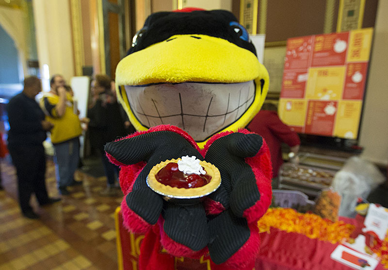 Cy the mascot with a cherry pie.