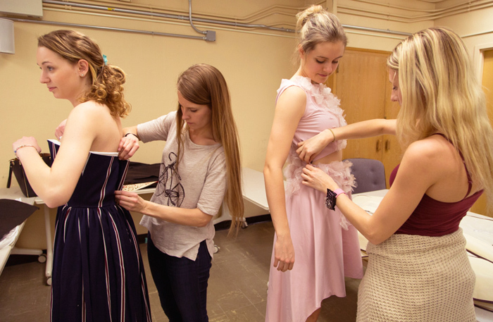 Female students adjust garments on student models during a fitti