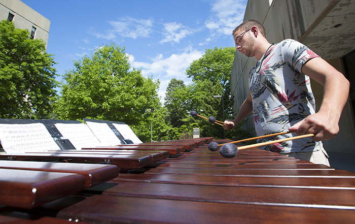 Male student plays the marimba outside in the sunshine