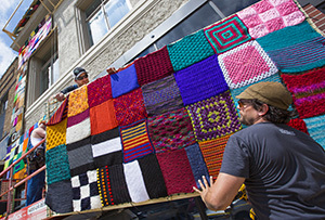Workers raise knit squares on a wood frame