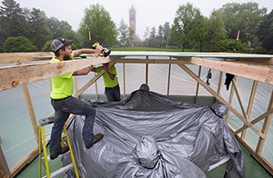 Workers build protective shed around outdoor sculpture