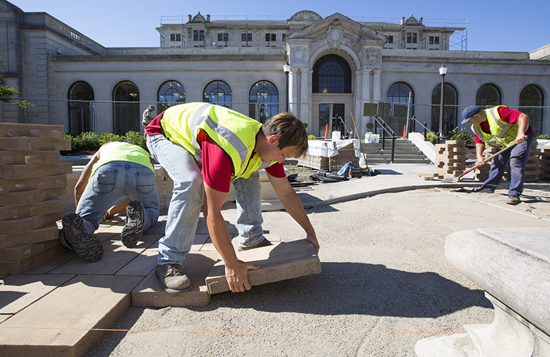 Workers install pavers in the MU fountain's plaza