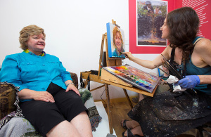 Artist paints portrait of seated woman