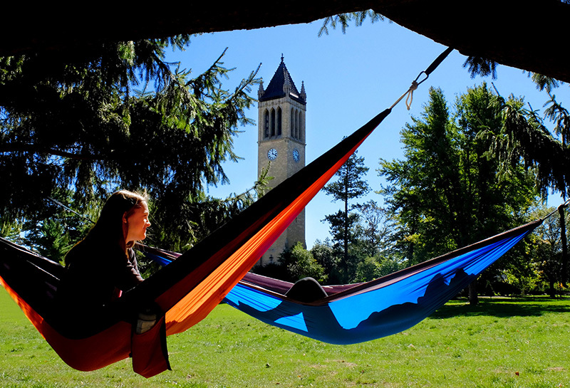Two female students hang out in hammocks near the campanile
