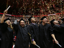 Four graudates in caps and gowns watch confetti fall