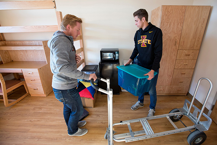 Two male students unload boxes from a moving cart