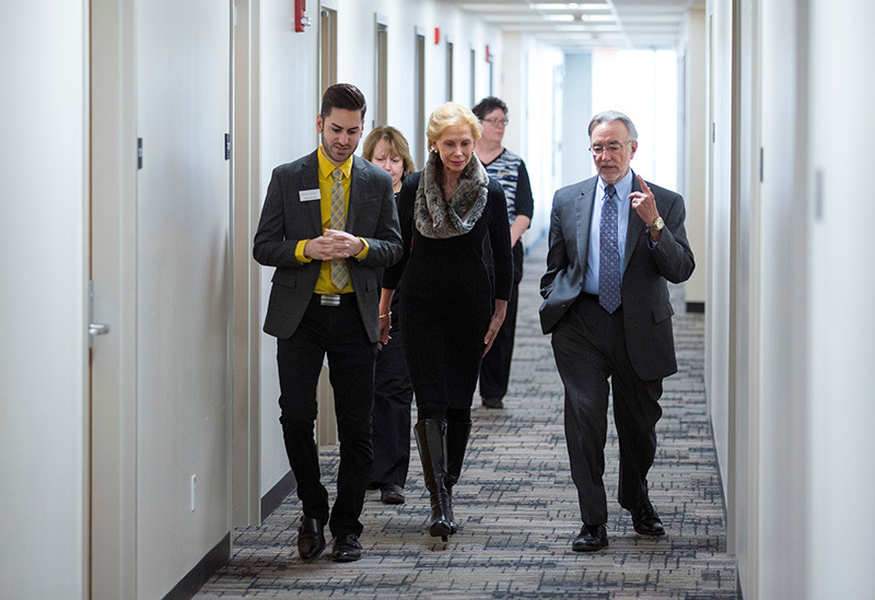 Group walks down residence hallway