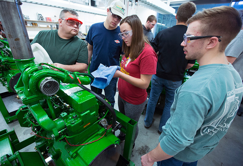 Four students work on a large tractor engine