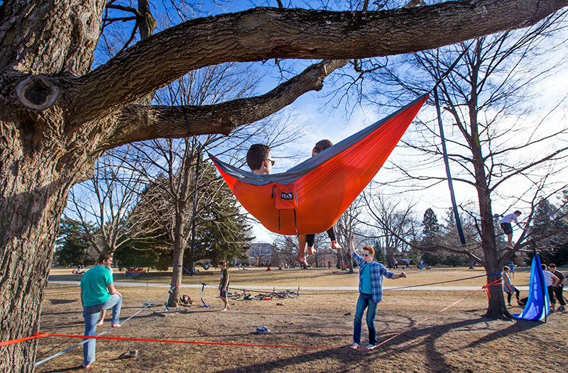 Two students walk a slack line while two observe from a hammock