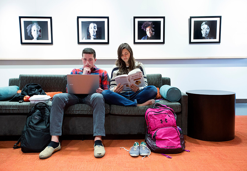 Male and female students study on a couch.