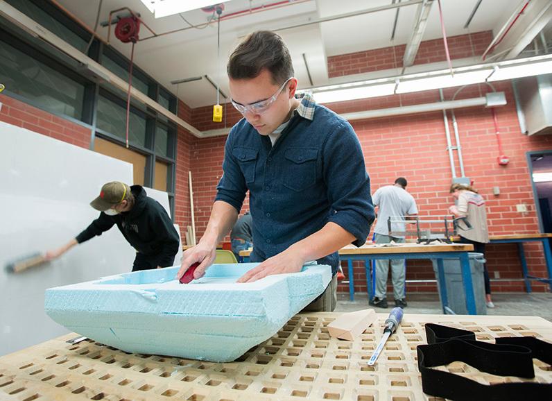 Male student cuts blue styrofoam form
