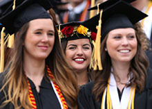 Three female students march in to their commencement ceremony