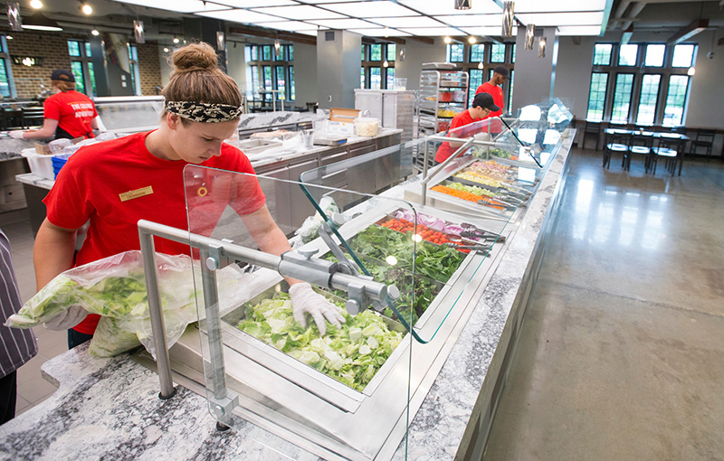 Female student loads lettuce into a salad bar in a new dining center