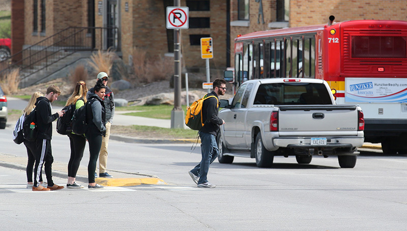 students collect on the Lincoln Way median as traffic passes
