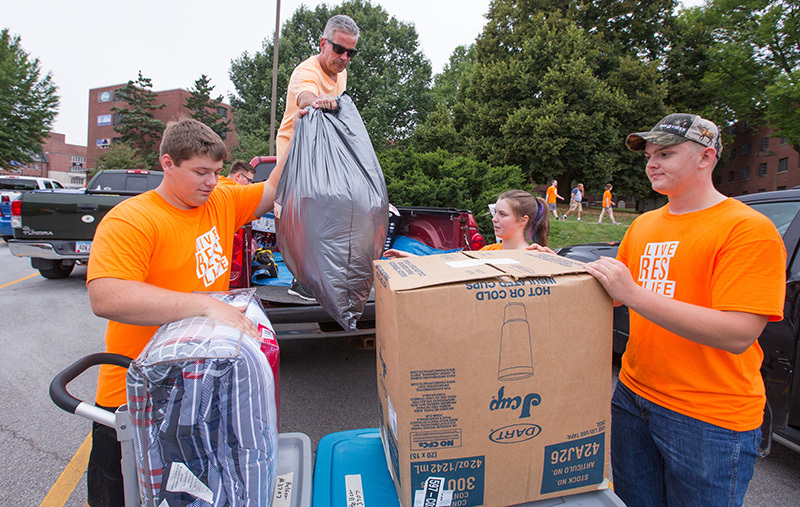 Student team in orange T-shirts unload a pickup truck