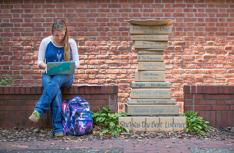 Female student studies in outdoor courtyard