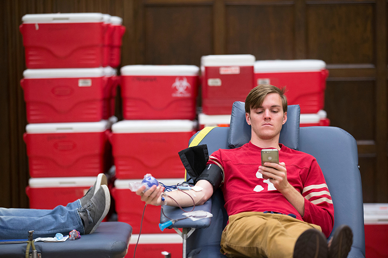 Seated male student is donating blood