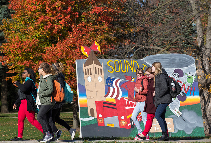 Female students pass a Homecoming banner on central campus