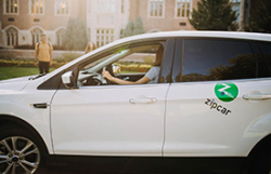 white sedan with Zipcar green dot logo on rear door