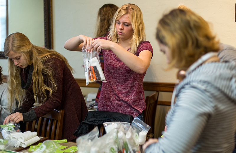 Female students fill plastic bags with hygiene products