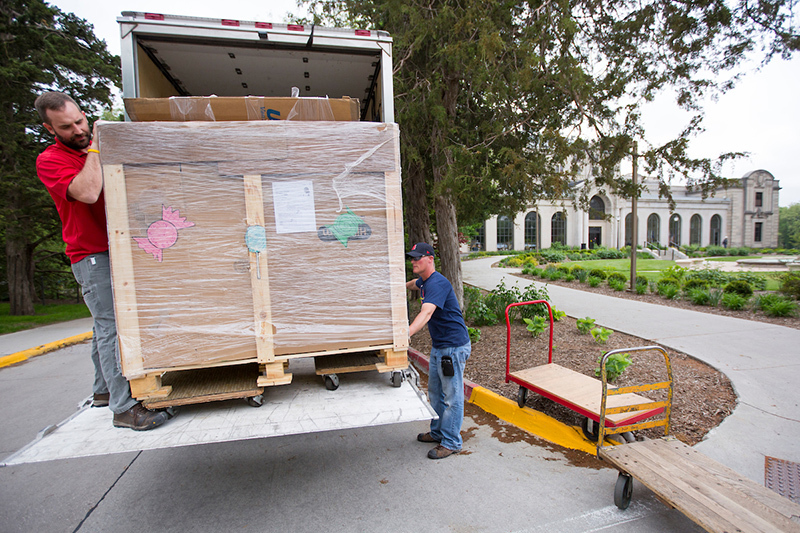 Two men unload a large crate from a box truck
