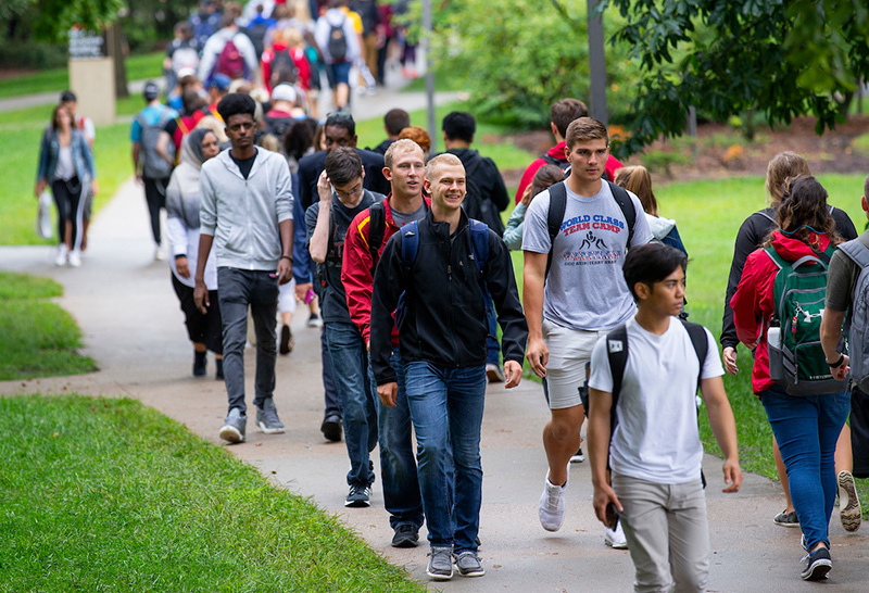 Students cross central campus on wet sidewalks.