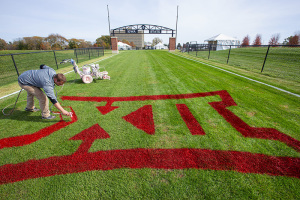 Conference logo being painted on the cross country course.