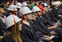 Construction engineering graduates attach tassels to hard hats