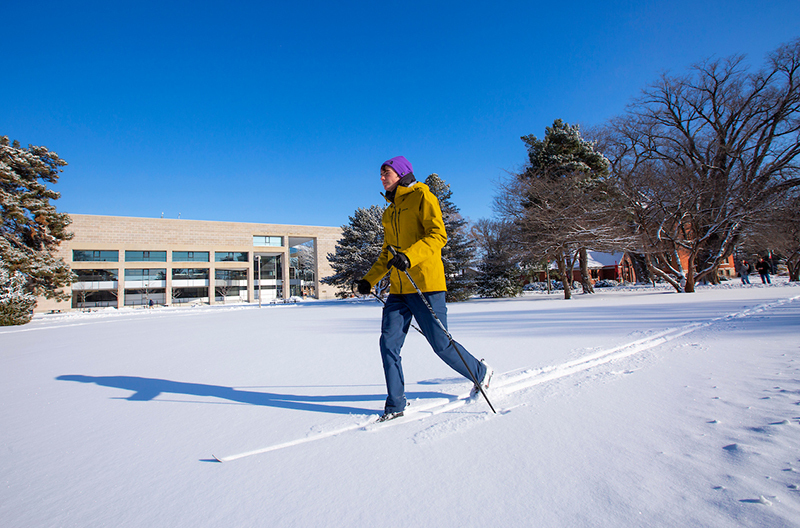 Male student cross country skis south of Parks Library