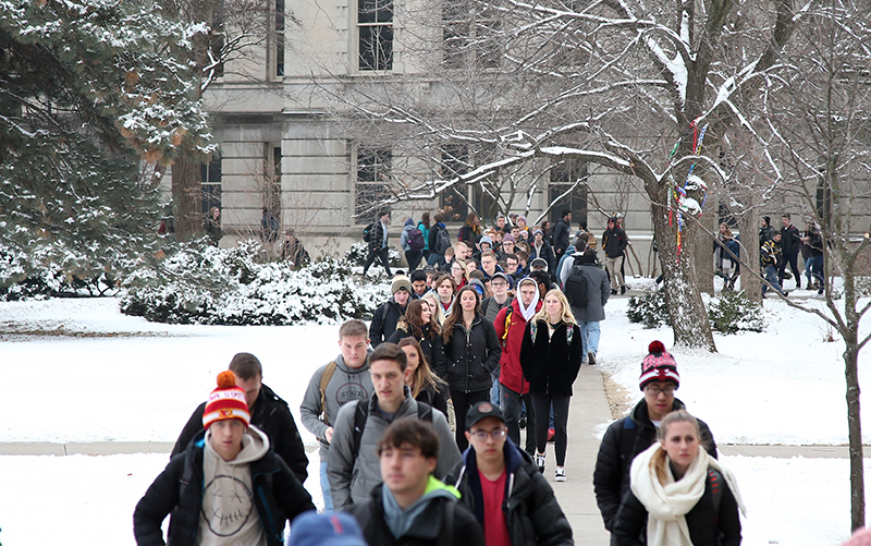 Students in caps and jackets move across a snowy campus lawn