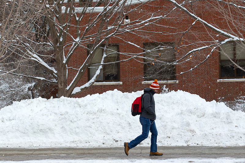 Male student passes snow pile adjacent to sidewalk