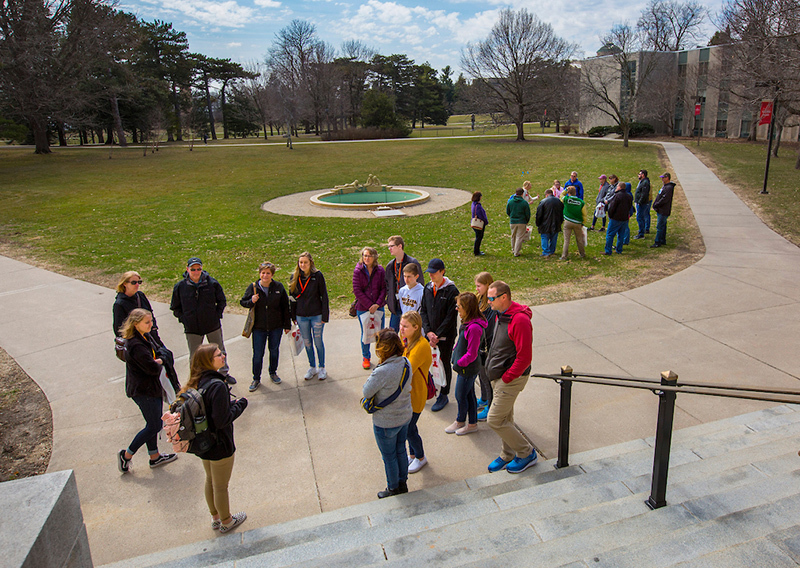Two tour groups congregate south of MacKay Hall