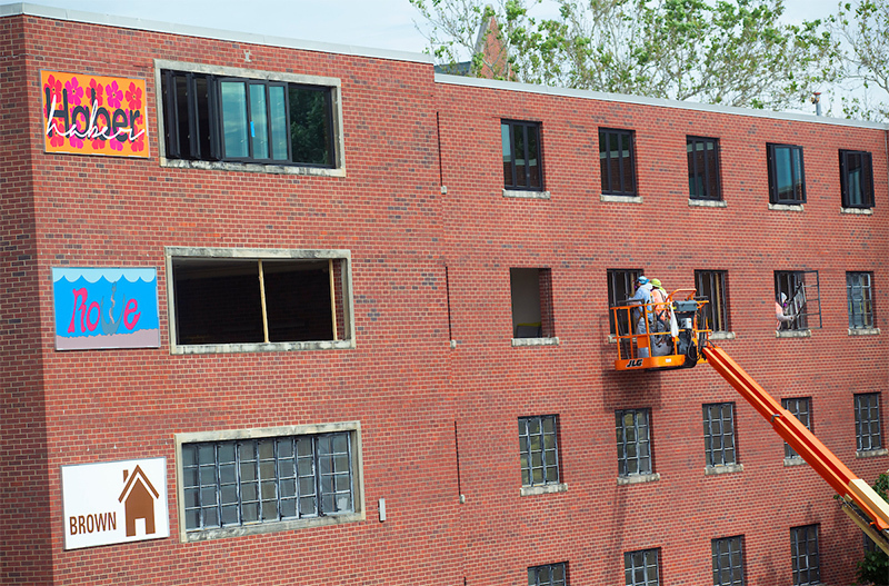 workers remove old windows from Helser Hall