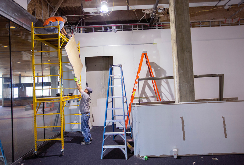 Drywall workers in the Brunnier museum space